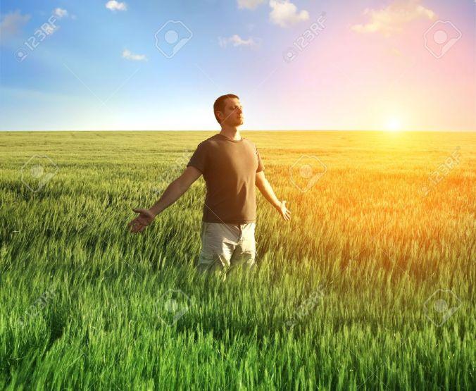 16008165-uomo-in-campo-di-grano-e-la-luce-solare-Archivio-Fotografico